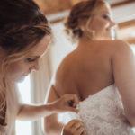 Trauzeugin knöpft Hochzeitskleid zu