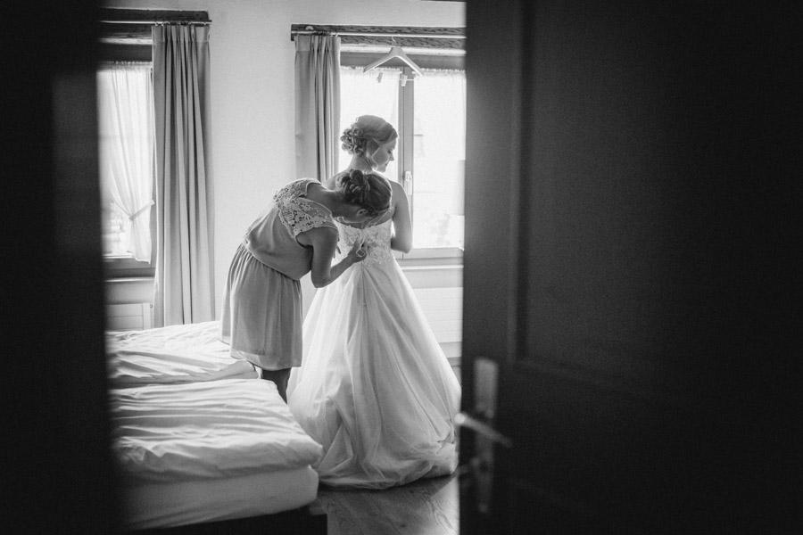 Trauzeugin hilft Braut beim Anziehen des Kleides